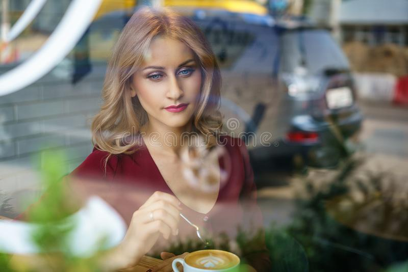 Όμορφη συνεδρίαση γυναικών από το παράθυρο σε έναν καφέ κατανάλωσης καφέδων στοκ φωτογραφία