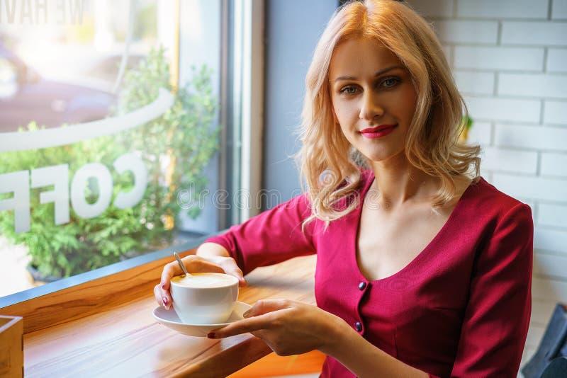 Όμορφη συνεδρίαση γυναικών από το παράθυρο σε έναν καφέ κατανάλωσης καφέδων στοκ εικόνες