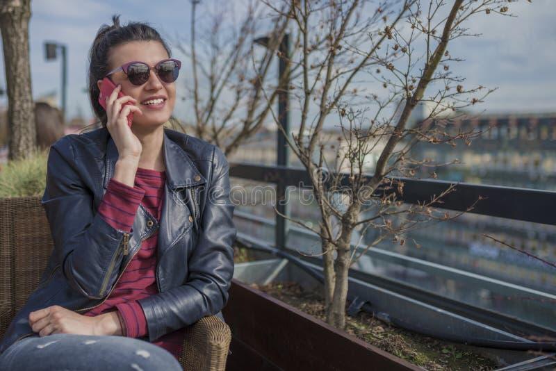 Όμορφη συνεδρίαση γυναικών χαμόγελου νέα υπαίθρια και ομιλία στο κινητό τηλέφωνο στοκ φωτογραφίες