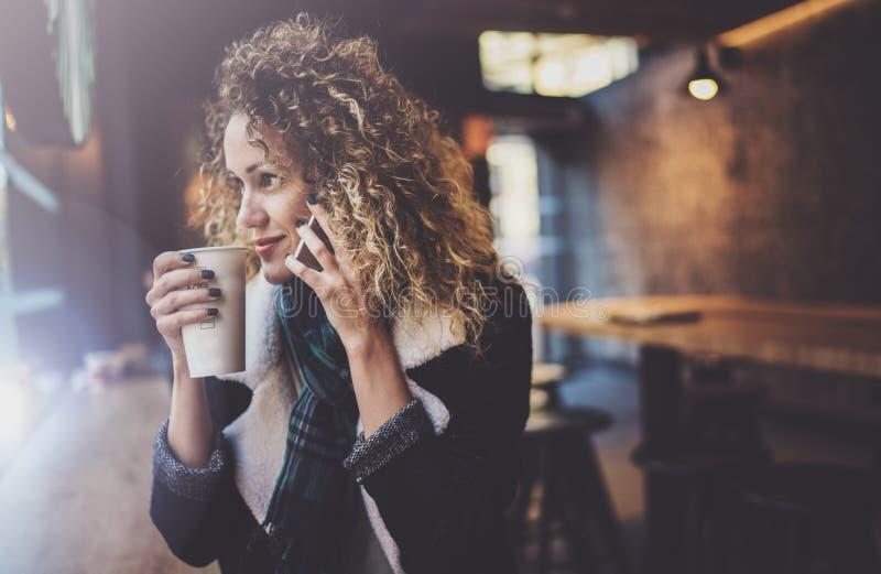 Όμορφη συνεδρίαση γυναικών χαμόγελου στον αστικό καφέ και ομιλία με τους φίλους μέσω του κινητού smartphone Περιστασιακό πορτρέτο στοκ εικόνες