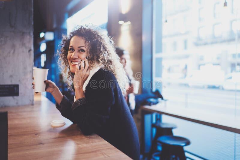Όμορφη συνεδρίαση γυναικών χαμόγελου στον αστικό καφέ και ομιλία με τους φίλους μέσω του κινητού smartphone Περιστασιακό πορτρέτο στοκ φωτογραφίες