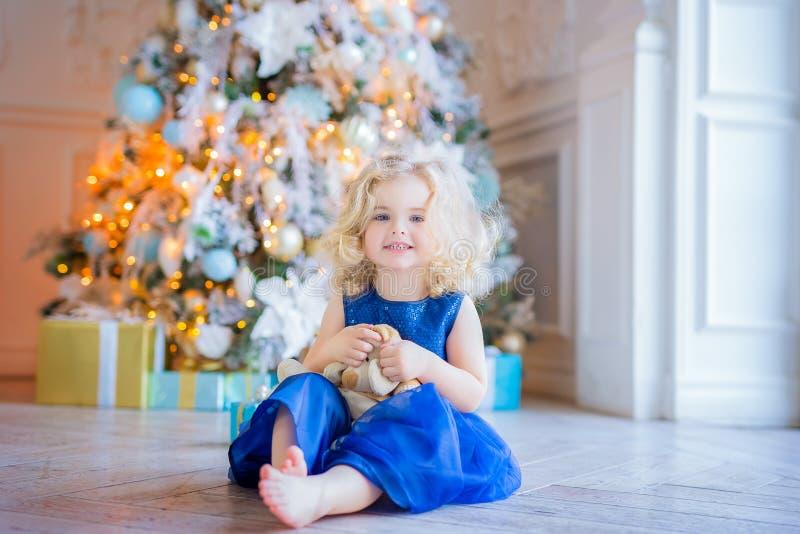 Όμορφη συνεδρίαση μικρών κοριτσιών κοντά στο χριστουγεννιάτικο δέντρο στοκ εικόνες
