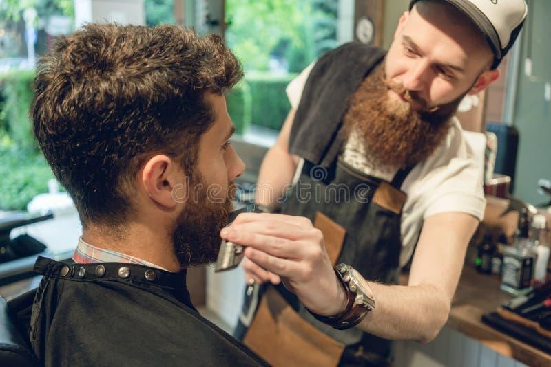 Όμορφη συνεδρίαση νεαρών άνδρων στην καρέκλα ενός barbershop στοκ εικόνα