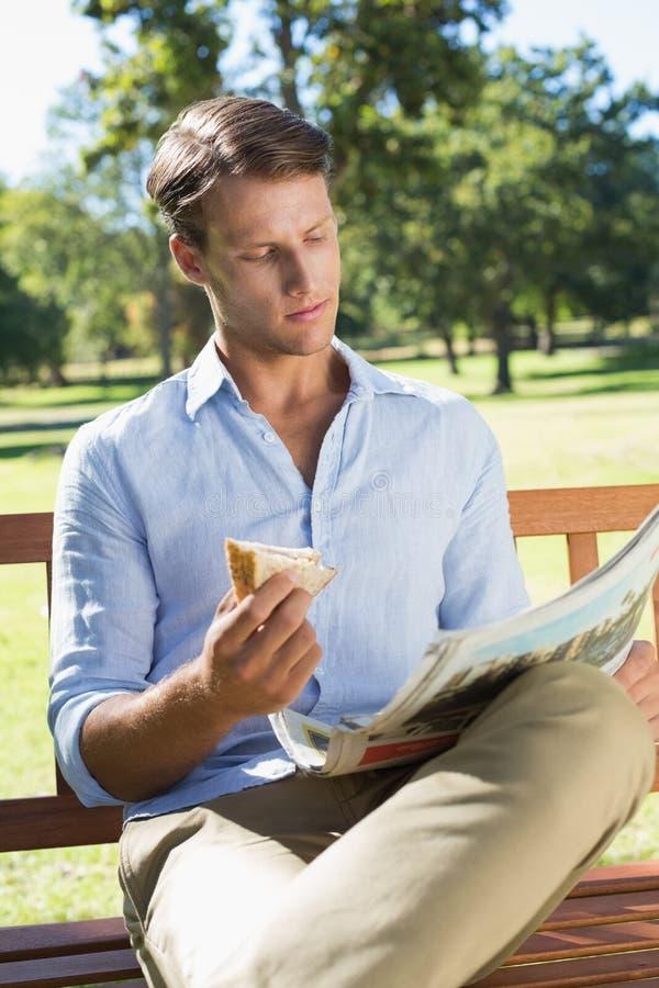Όμορφη συνεδρίαση ατόμων στον πάγκο πάρκων που τρώει το σάντουιτς και που διαβάζει το έγγραφο στοκ εικόνα