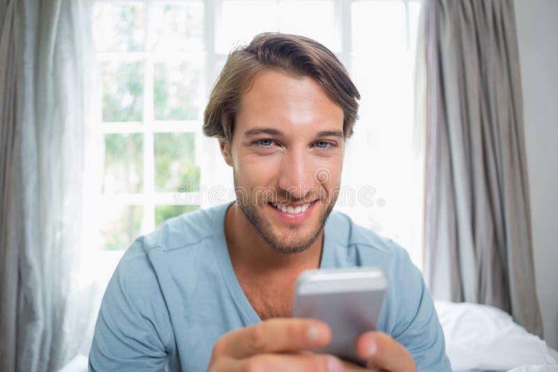 Όμορφη συνεδρίαση ατόμων στο κρεβάτι που στέλνει ένα μήνυμα κειμένου στοκ εικόνες