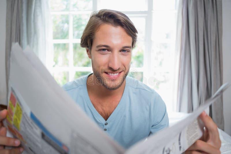 Όμορφη συνεδρίαση ατόμων χαμόγελου στο κρεβάτι που διαβάζει την εφημερίδα στοκ εικόνα