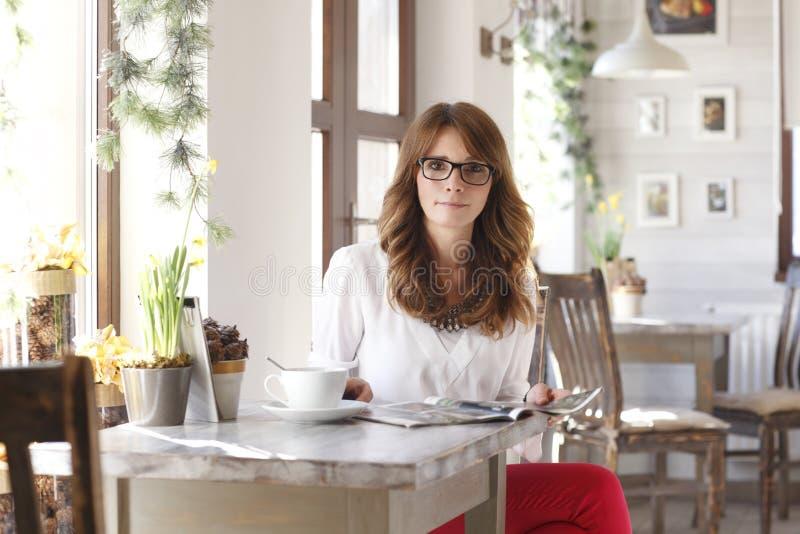 Όμορφη συνεδρίαση γυναικών στο γραφείο στη καφετερία στοκ φωτογραφίες