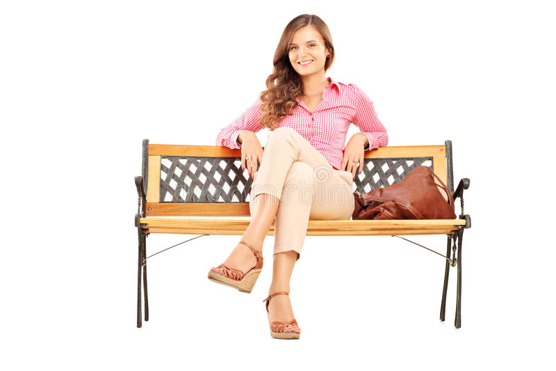 Όμορφη συνεδρίαση γυναικών brunette σε έναν ξύλινο πάγκο και να φανεί α στοκ εικόνες