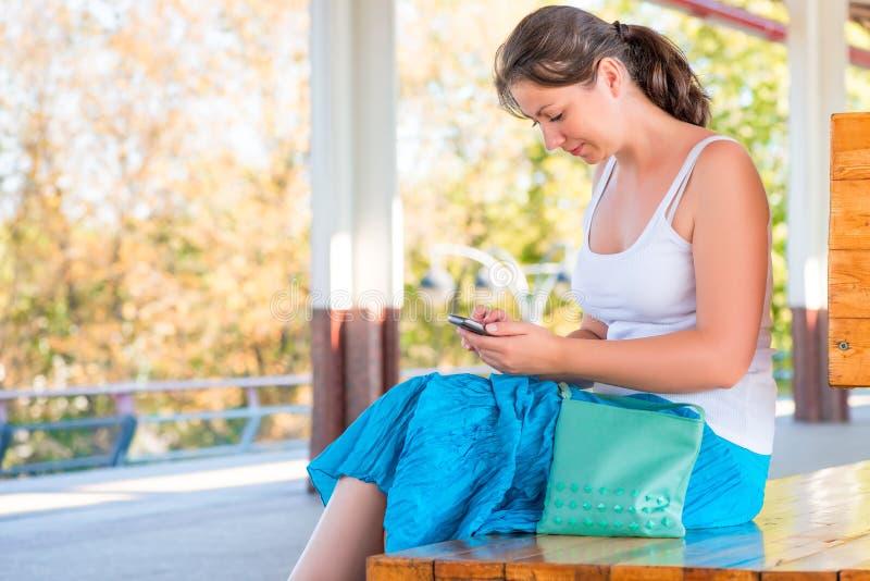 Όμορφη συνεδρίαση κοριτσιών σε έναν πάγκο με το τηλέφωνο στοκ εικόνες