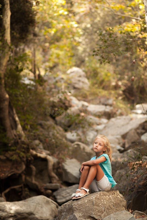 Όμορφη συνεδρίαση κοριτσιών στην πέτρα στοκ εικόνα
