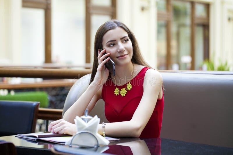 Όμορφη συνεδρίαση κοριτσιών brunette σε μια καφετερία στοκ εικόνα με δικαίωμα ελεύθερης χρήσης