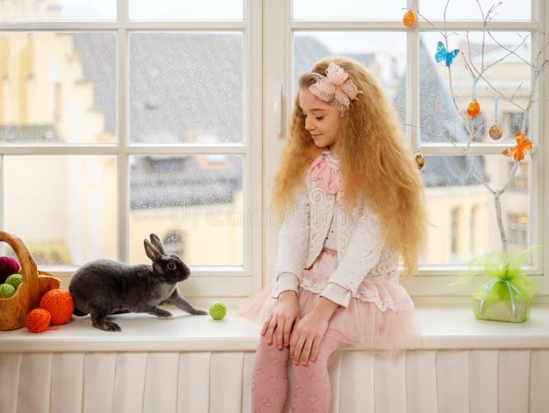 Όμορφη συνεδρίαση νέων κοριτσιών σε ένα windowsill και παιχνίδι με το λαγουδάκι Πάσχας στοκ εικόνες με δικαίωμα ελεύθερης χρήσης