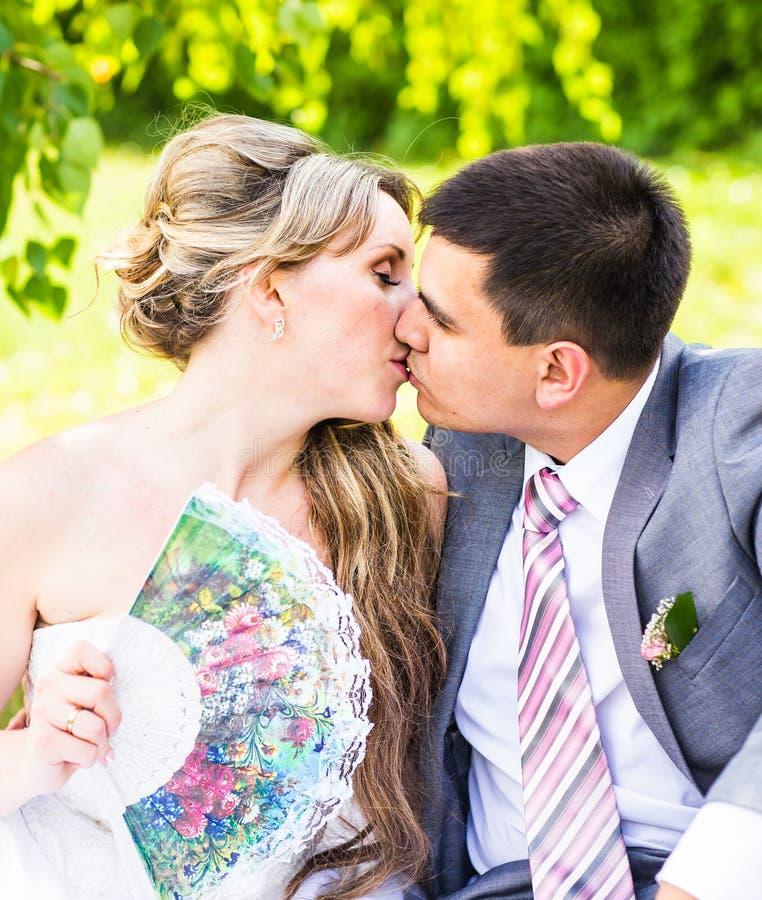 Όμορφη συνεδρίαση νυφών και νεόνυμφων στη χλόη και φίλημα γαμήλιες νεολαίες ζευγών στοκ φωτογραφίες