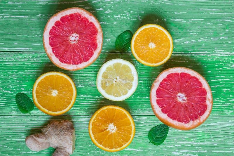 Όμορφη σύνθεση του φρέσκου χυμού από πορτοκάλι στο γυαλί, λεμόνι, ora στοκ φωτογραφία