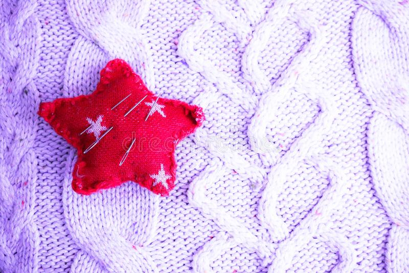 Όμορφη σύσταση ενός μαλακού θερμού φυσικού πουλόβερ, ενός υφάσματος με ένα πλεκτό σχέδιο και ενός μαξιλαριού βελόνων για το ράψιμ στοκ εικόνα