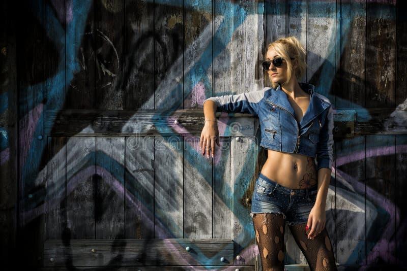 Όμορφη τοποθέτηση γυναικών στην καθιερώνουσα τη μόδα μόδα τζιν στοκ φωτογραφίες με δικαίωμα ελεύθερης χρήσης