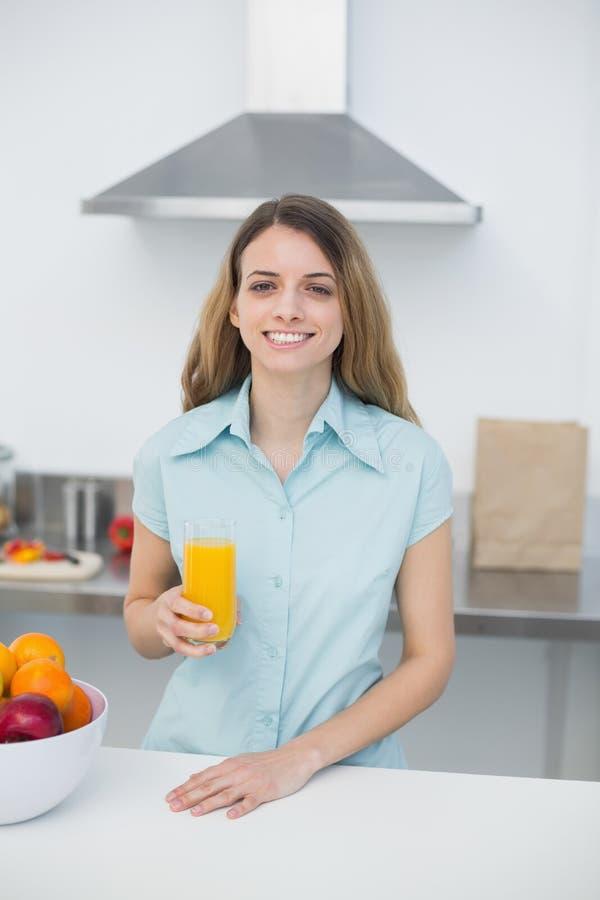 Όμορφη τοποθέτηση γυναικών brunette που στέκεται στην κουζίνα που κρατά ένα ποτήρι του χυμού από πορτοκάλι στοκ εικόνα