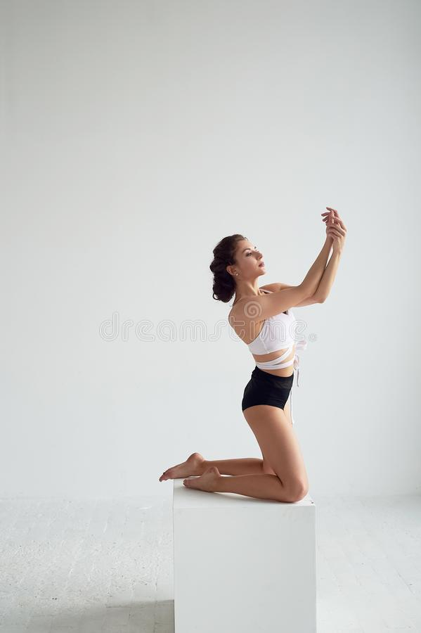Όμορφη τοποθέτηση χορευτών μπαλέτου στο στούντιο που εκτελεί την εκτροπή στην πλάτη και που κλίνει σε έναν μεγάλο κύβο στοκ φωτογραφία με δικαίωμα ελεύθερης χρήσης