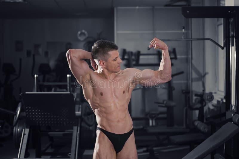 Όμορφη τοποθέτηση bodybuilder στη γυμναστική, τέλειο μυϊκό αρσενικό σώμα στοκ εικόνα με δικαίωμα ελεύθερης χρήσης