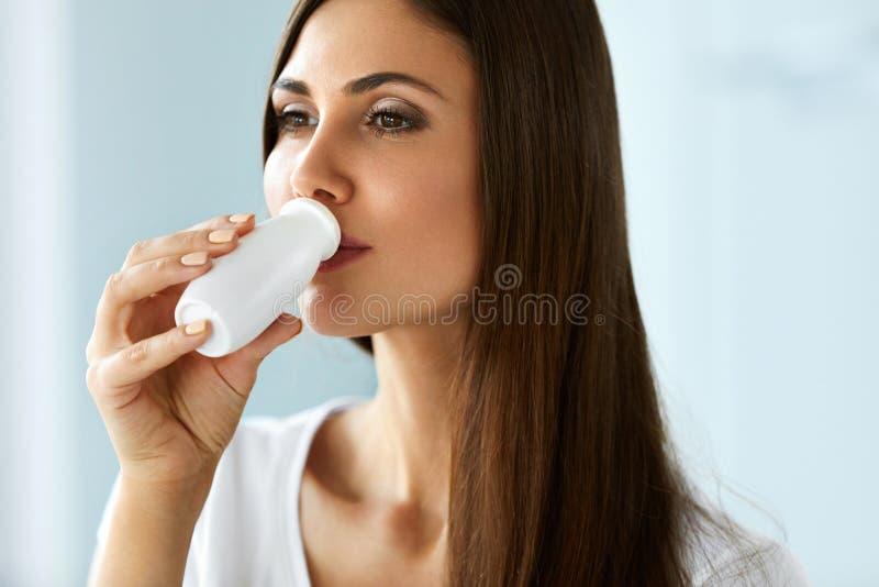 Όμορφη υγιής γυναίκα που πίνει το φυσικό γιαούρτι, γαλακτοκομικό προϊόν στοκ εικόνες