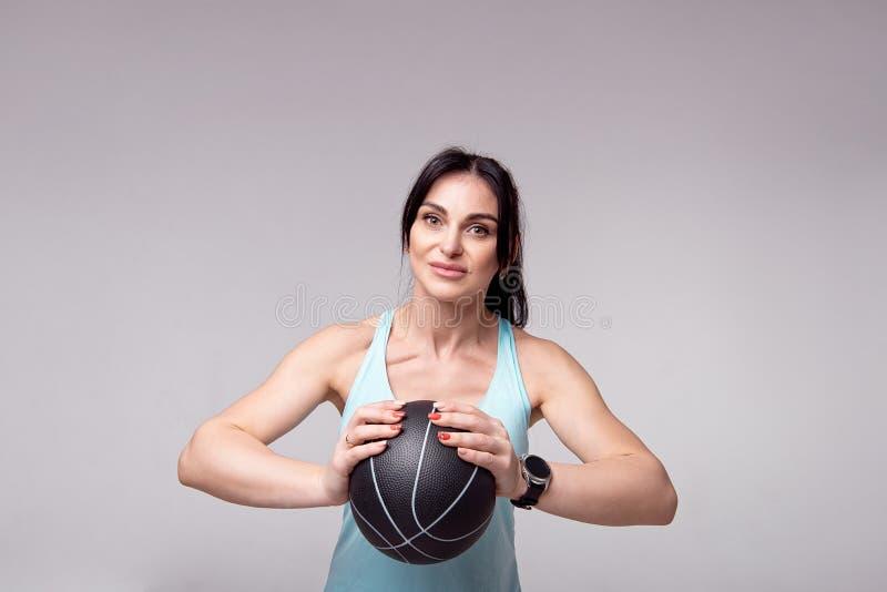Όμορφη φίλαθλη γυναίκα που κάνει τις στάσεις οκλαδόν με τη σφαίρα MED που απομονώνονται στο άσπρο υπόβαθρο E στοκ εικόνες