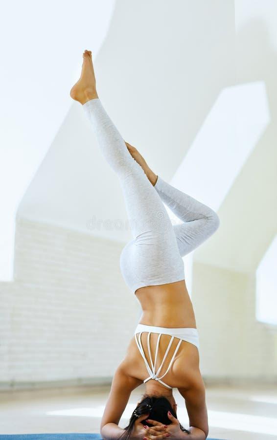 Όμορφη φίλαθλη κατάλληλη νέα γυναίκα που επιλύει στο εσωτερικό ενάντια στον άσπρο τοίχο, που κάνει τις ασκήσεις γιόγκας Υγιής τρό στοκ εικόνες με δικαίωμα ελεύθερης χρήσης