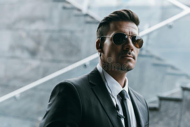 όμορφη φρουρά ασφάλειας που στέκεται στα γυαλιά ηλίου στοκ εικόνες