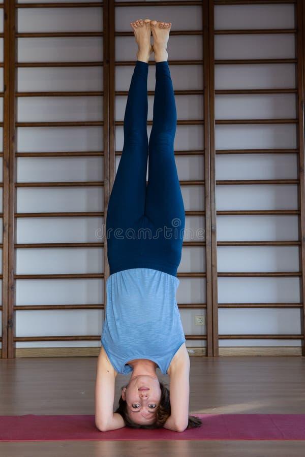 Όμορφη φωτογραφία της νέας κυρίας που στέκεται στην άσκηση γεφυρών ενώ η εν ενεργεία γιόγκα θέτει στο χαλί γιόγκας στοκ φωτογραφίες