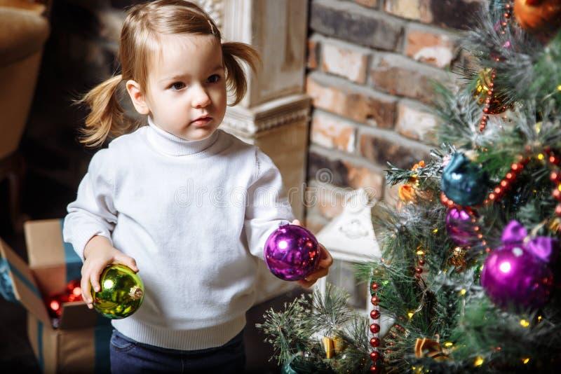 Όμορφη φωτογραφία του χαριτωμένου μικρού κοριτσιού 2 έτη που διακοσμούν το χριστουγεννιάτικο δέντρο στο σπίτι στοκ φωτογραφίες με δικαίωμα ελεύθερης χρήσης