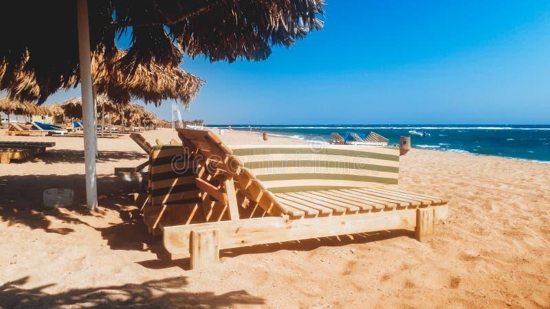Όμορφη φωτογραφία των παλαιών ξύλινων κρεβατιών ή των αργοσχόλων ήλιων στην κενή παραλία στην ηλιόλουστη θυελλώδη ημέρα στοκ φωτογραφία