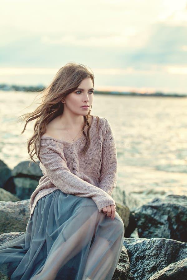 Όμορφη χαλάρωση γυναικών στην ωκεάνια ακτή τη νύχτα στοκ εικόνα με δικαίωμα ελεύθερης χρήσης