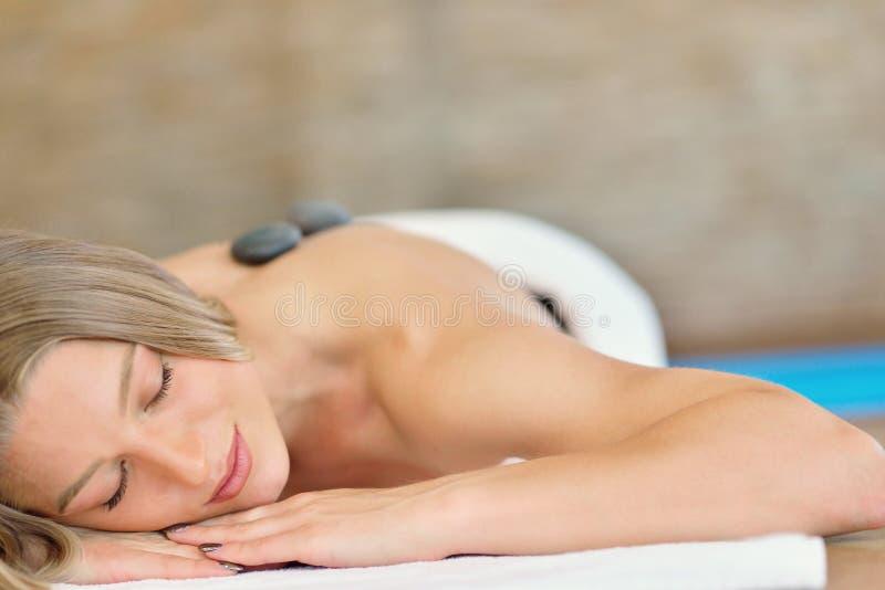 Όμορφη χαλάρωση γυναικών στο σαλόνι SPA με τις καυτές πέτρες στο σώμα Θεραπεία θεραπείας ομορφιάς στοκ εικόνες