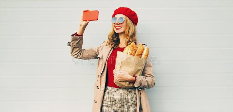 Όμορφη χαμογελαστή γυναίκα που τραβάει φωτογραφία από το τηλέφωνο κρατώντας τσάντα από παντοπωλείο για ψώνια με μακρύ λευκό ψωμί  στοκ φωτογραφίες