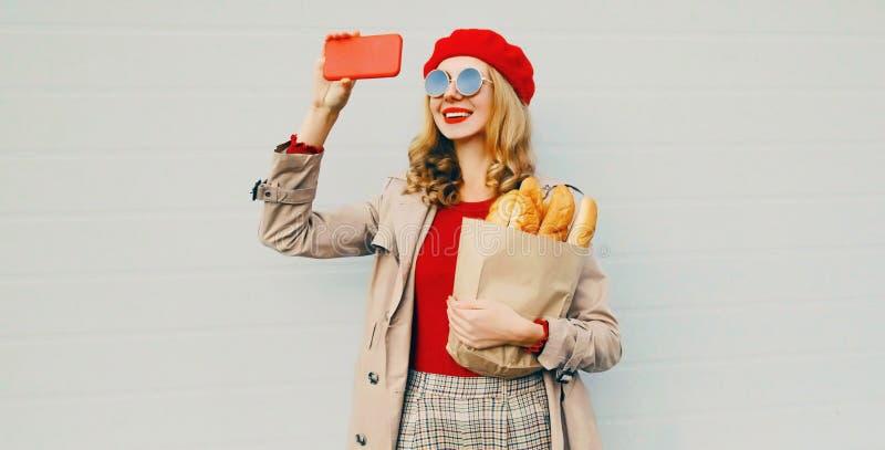 Όμορφη χαμογελαστή γυναίκα που τραβάει φωτογραφία από το τηλέφωνο κρατώντας τσάντα από παντοπωλείο για ψώνια με μακριά λευκή μπαγ στοκ φωτογραφίες