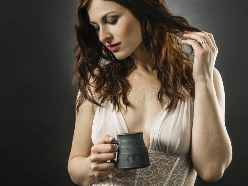 Όμορφη χαμογελαστή κοκκινομάλλα που πίνει καφέ στοκ εικόνες