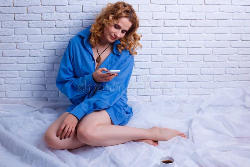 Όμορφη χαμογελώντας γυναίκα με τη σγουρή τρίχα που διαβάζει ένα μήνυμα σε την στοκ φωτογραφίες