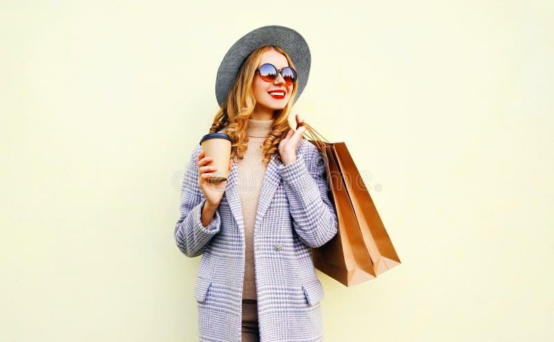 Όμορφη χαμογελώντας γυναίκα πορτρέτου με τις τσάντες αγορών, που κρατά το φλυτζάνι καφέ, που φορά το ρόδινο παλτό, στρογγυλό καπέ στοκ εικόνες