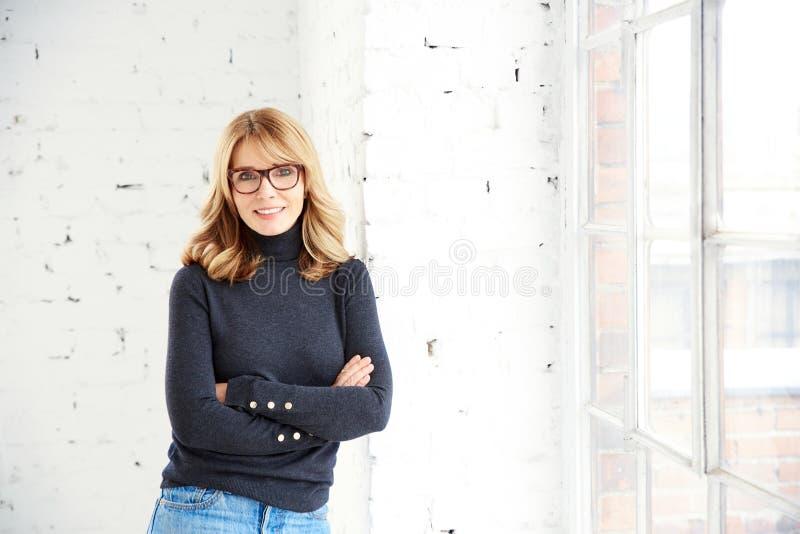 Όμορφη χαμογελώντας γυναίκα που στέκεται με τα όπλα που διασχίζονται χαλαρώνοντας στο παράθυρο στοκ φωτογραφία