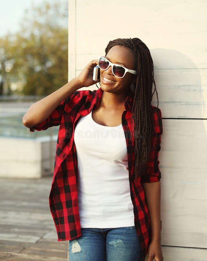 Όμορφη χαμογελώντας αφρικανική γυναίκα που μιλά στο smartphone στην πόλη στοκ εικόνα