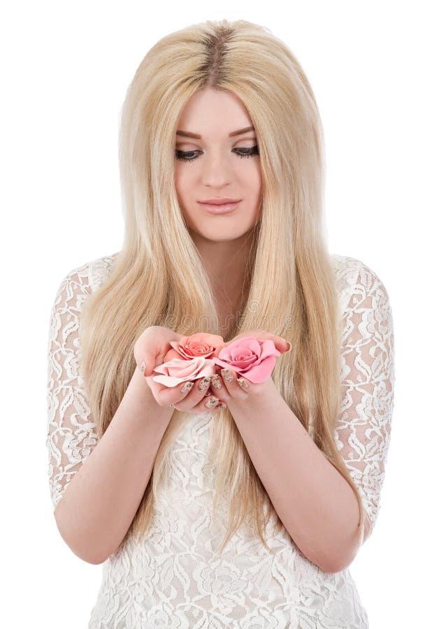 Όμορφη χαμογελώντας γυναίκα γυναικών που εξετάζει τα ρόδινα τριαντάφυλλα στοκ εικόνες με δικαίωμα ελεύθερης χρήσης