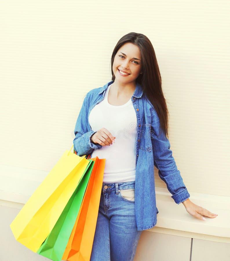 Όμορφη χαμογελώντας γυναίκα με τις ζωηρόχρωμες τσάντες αγορών στα ενδύματα τζιν στοκ εικόνα με δικαίωμα ελεύθερης χρήσης
