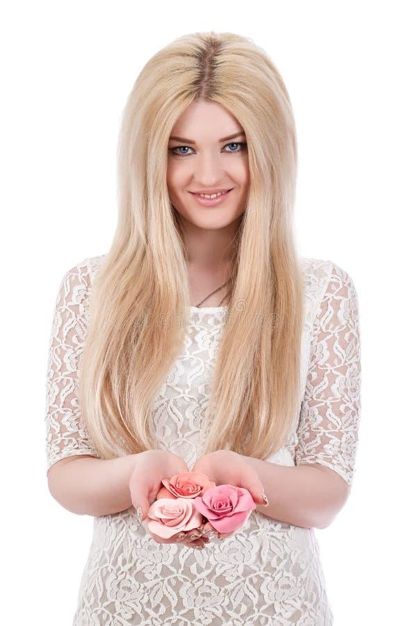 Όμορφη χαμογελώντας γυναίκα που κρατά τα ρόδινα τριαντάφυλλα στοκ εικόνες