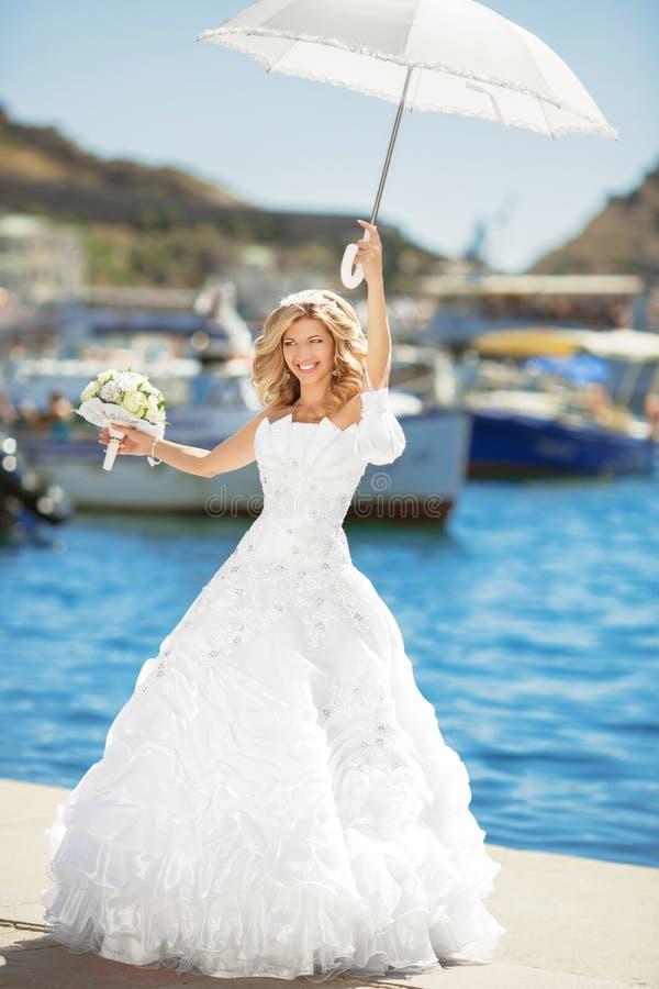 Όμορφη χαμογελώντας νύφη στο γαμήλιο φόρεμα με την άσπρη ομπρέλα pos στοκ εικόνες