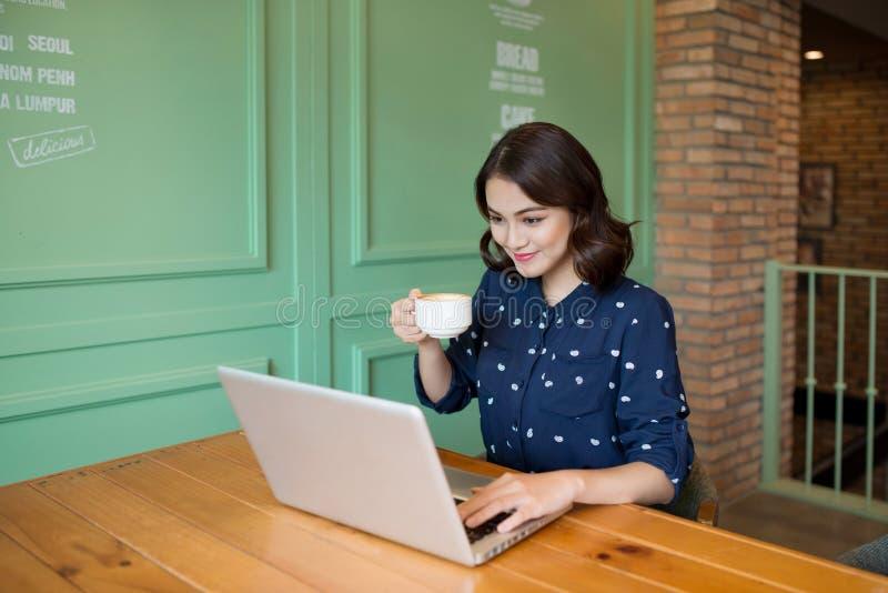 Όμορφη χαριτωμένη ασιατική νέα επιχειρηματίας στον καφέ, που χρησιμοποιεί lapt στοκ φωτογραφίες