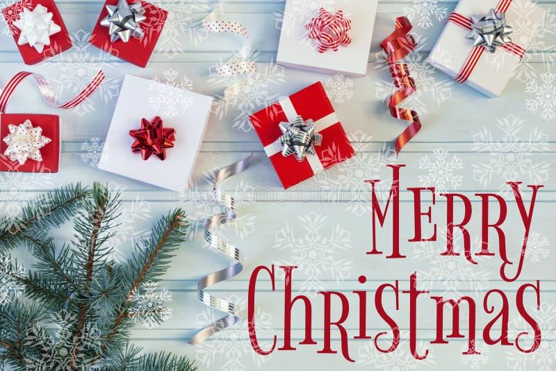 Όμορφη Χαρούμενα Χριστούγεννα επιγραφής Εδώ κοντά, σε ένα μπλε υπόβαθρο υπάρχει ένας κλάδος έλατου και πολλά δώρα Μικρός κόκκινος στοκ εικόνα