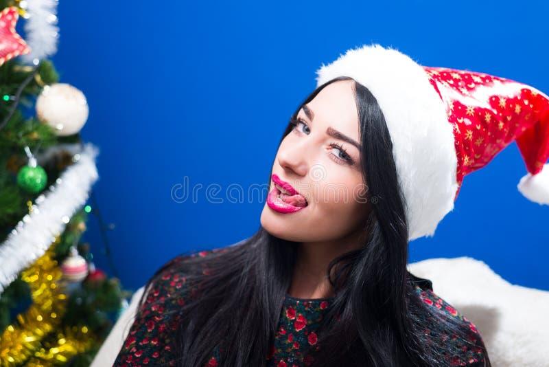 Όμορφη χαρούμενη νέα κυρία στο γλείψιμο καπέλων Santa στοκ εικόνες