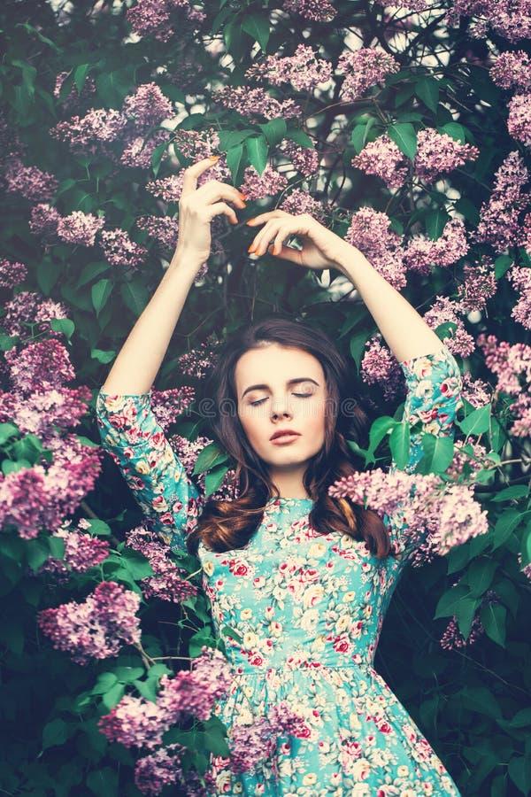 Όμορφη χαλάρωση γυναικών στα λουλούδια στοκ φωτογραφία