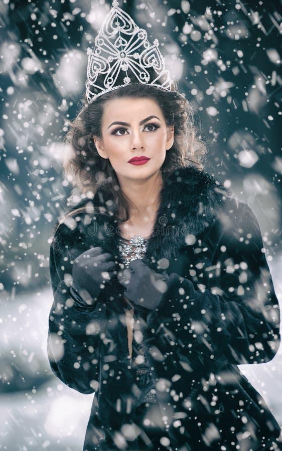 Όμορφη χειμερινή βασίλισσα παραμυθιού στο δάσος με τη λαμπιρίζοντας τιάρα και το κομψό μαύρο παλτό γουνών στοκ φωτογραφίες