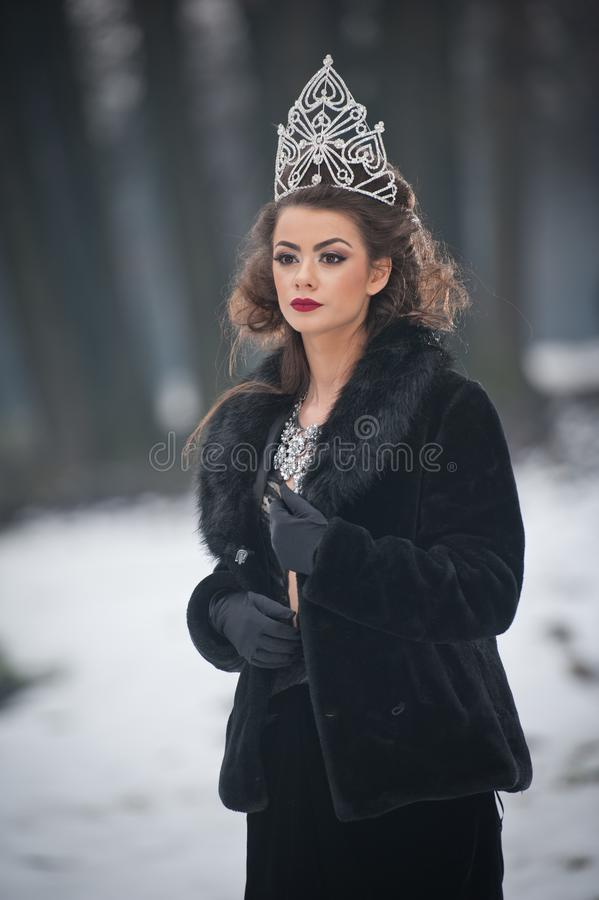 Όμορφη χειμερινή βασίλισσα παραμυθιού στο δάσος με τη λαμπιρίζοντας τιάρα και το κομψό μαύρο παλτό γουνών στοκ εικόνα