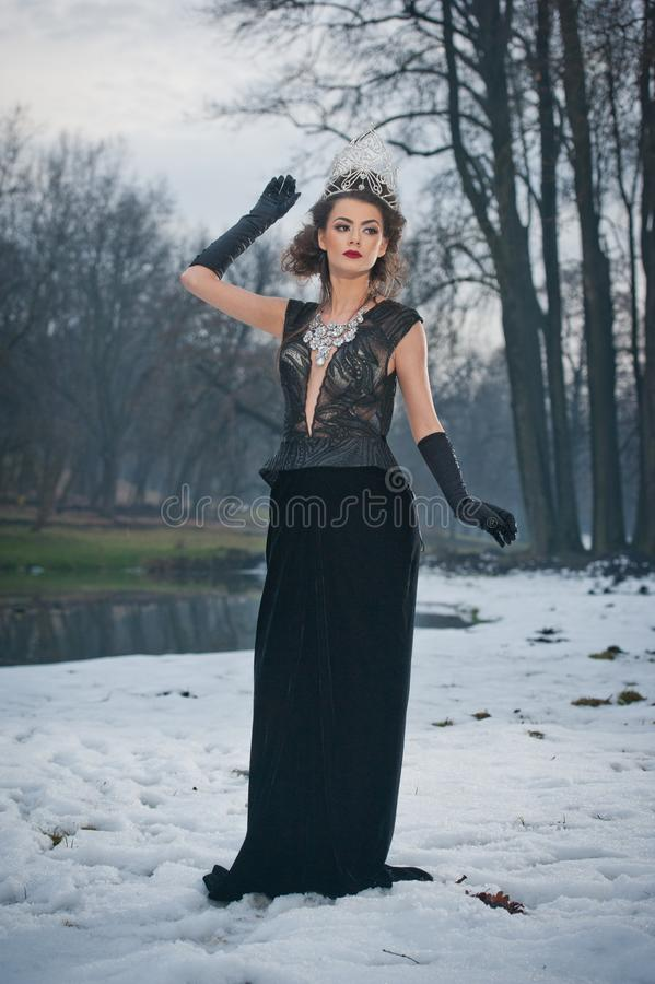 Όμορφη χειμερινή βασίλισσα παραμυθιού στο δάσος με τη λαμπιρίζοντας τιάρα και το κομψό μαύρο παλτό γουνών στοκ φωτογραφία